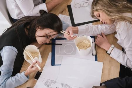 top view of businesswomen sleeping on table with boxes of noodles with chopsticks at office