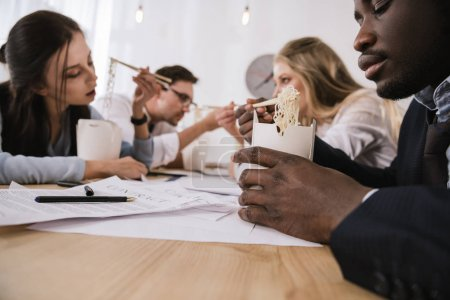 close-up shot of businesspeople eating noodles together at office