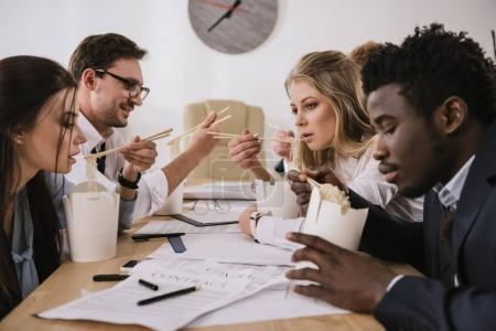 overorked businesspeople eating noodles in conference hall at office on deadline