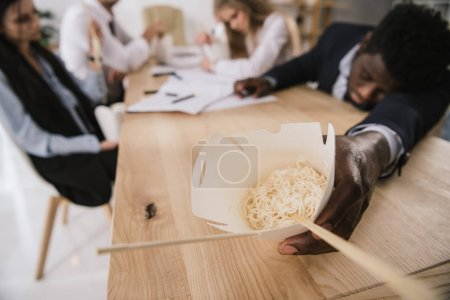 close-up shot of sleeping businessman in conference room with box of noodles in hand