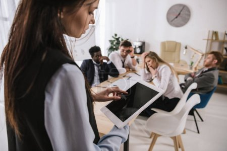 businesswoman using digital tablet with blurred coworkers sitting in conference hall on background