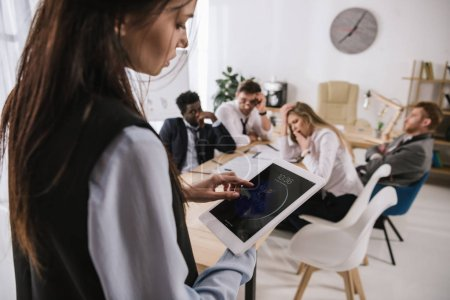 businesswoman using tablet at office with colleagues sitting blurred on background