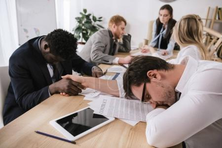 sleeping business partners shaking hands in conference hall