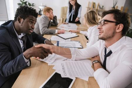 untidy overworked businessmen shaking hands while sitting at conference hall