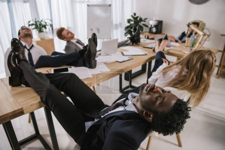 exhausted businesspeople sleeping in conference hall with feet on table