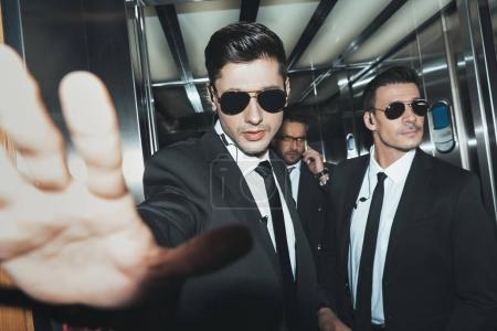 bodyguards stopping paparazzi when celebrity talking by smartphone