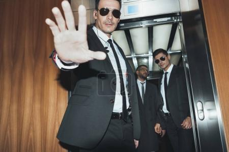 Photo for Bodyguard obstructing paparazzi when celebrity going into elevator - Royalty Free Image