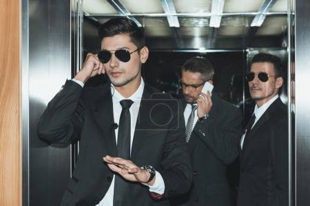 bodyguard listening security earpiece and businessman talking by smartphone