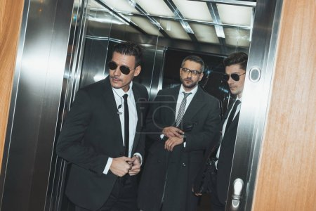 Photo for Bodyguards looking out from elevator and businessman looking at watch - Royalty Free Image