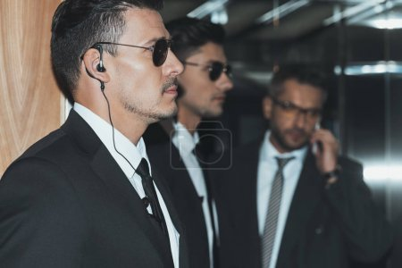 Photo for Profile of bodyguards in sunglasses and businessman talking by smartphone - Royalty Free Image