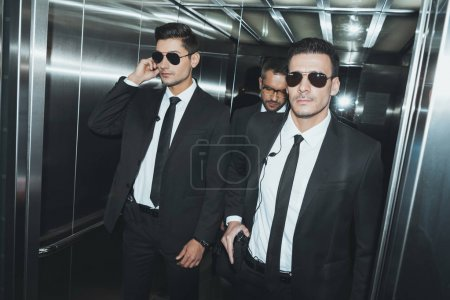 two bodyguards and politician standing in elevator