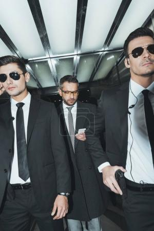 Photo for Businessman looking at smartphone while standing with bodyguards in elevator - Royalty Free Image
