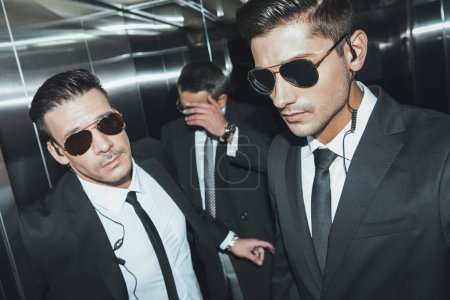 Photo for Celebrity covering face by hand in elevator - Royalty Free Image