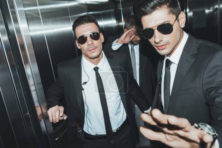 bodyguards stopping paparazzi and celebrity covering face with hand in elevator