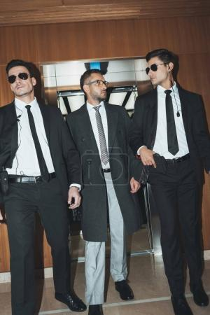 Photo for Bodyguards and businessman walking from elevator in business center - Royalty Free Image