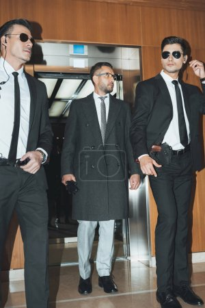 businessman going out from elevator with two bodyguards