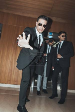 bodyguard in sunglasses stopping paparazzi when celebrity going out from elevator