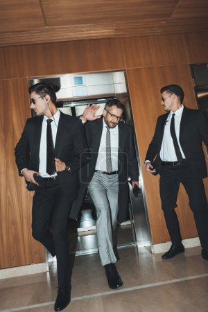 celebrity going out from elevator and covering face by hand