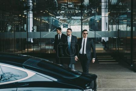 businessman and two bodyguards walking to car