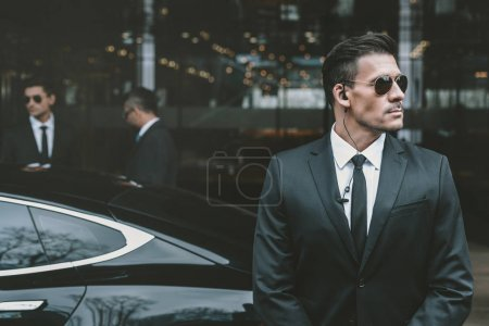 bodyguard standing at businessman car and reviewing territory