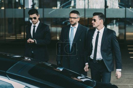 Photo for Two bodyguards going with businessman to black car - Royalty Free Image