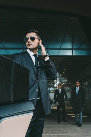 Photo pour Garde du corps, ouverture de porte de voiture pour l'homme d'affaires et en écoutant écouteur de sécurité - image libre de droit