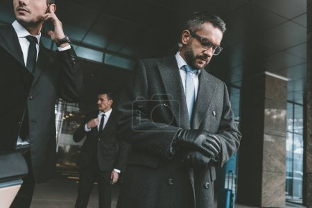 businessman looking at watch and standing with bodyguards