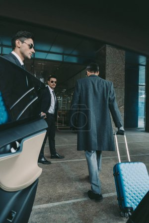 businessman going with blue travel bag to airport