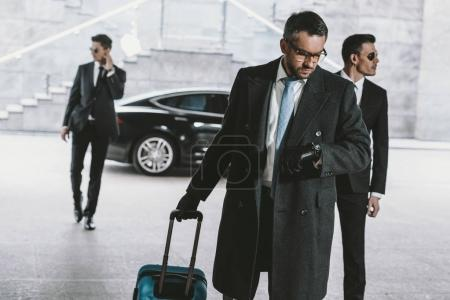 businessman going with travel bag and looking at watch