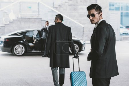 businessman going with blue wheeled bag to car
