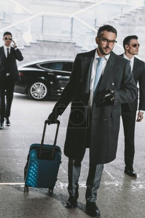 handsome businessman walking with travel bag from car and looking at watch