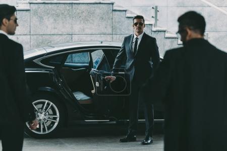 Photo pour Garde du corps en ouvrant la portière de la voiture à l'homme d'affaires de lunettes de soleil - image libre de droit