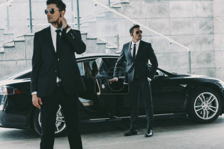 bodyguards in sunglasses standing at car and waiting for politician