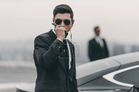 handsome bodyguard in sunglasses talking by portable radio