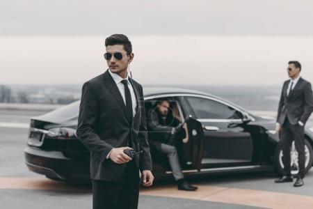 Photo pour Garde du corps avec commandes radio portative sur la voiture de l'homme d'affaires - image libre de droit