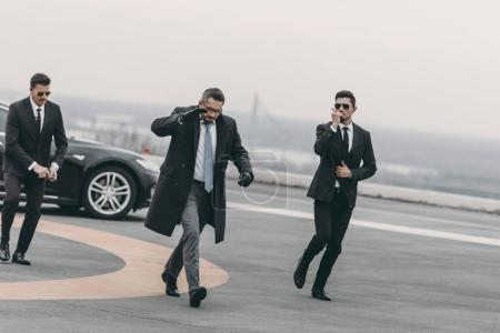 Photo for Businessman covering his face with hand and walking with bodyguards - Royalty Free Image