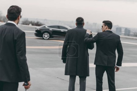 Photo for Rear view of two bodyguards walking with businessman to car - Royalty Free Image
