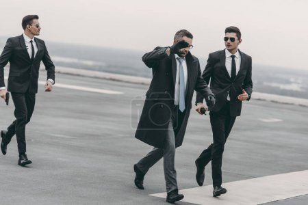 businessman covering his face with hand and walking with bodyguards on helipad