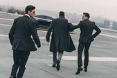 rear view of two bodyguards going with businessman to car