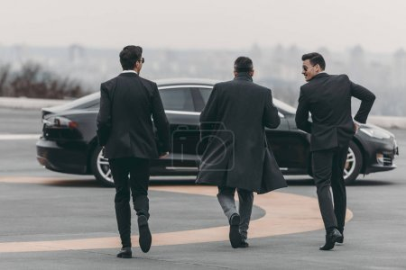 Photo for Rear view of businessman and bodyguards walking to car at helipad - Royalty Free Image