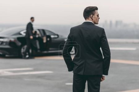 Photo pour Vue arrière du garde du corps en costume et lunettes de soleil - image libre de droit