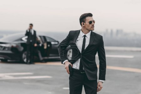 Photo for Handsome bodyguard with security earpiece putting hand on gun - Royalty Free Image