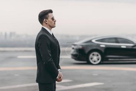 Photo for Bodyguard in suit with security earpiece standing close to politician car - Royalty Free Image