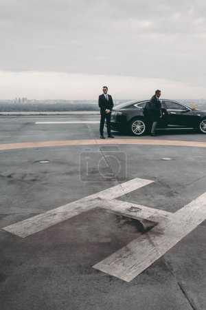 Photo for Bodyguard and businessman standing near car on helipad - Royalty Free Image