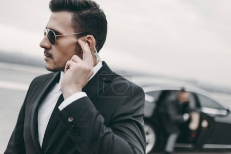handsome bodyguard of businessman listening message with security earpiece