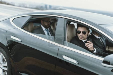 Photo for Bodyguards and businessman sitting in a black car - Royalty Free Image