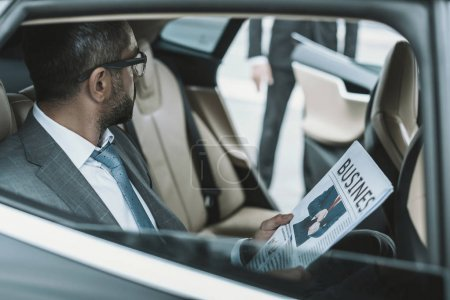 Photo for Businessman sitting in a car and holding newspaper - Royalty Free Image