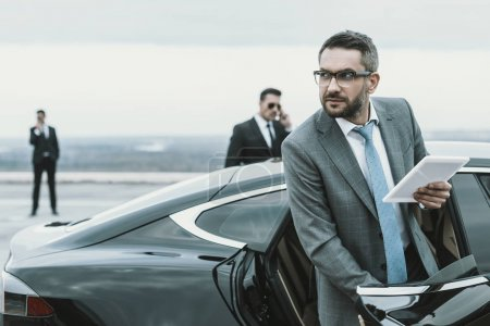businessman going out from car and holding tablet in hand