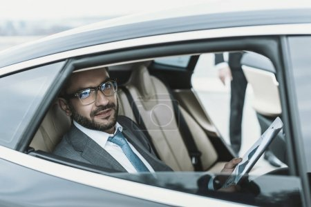 businessman sitting in a car with newspaper and looking away