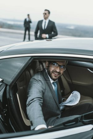 smiling businessman in glasses going out from car